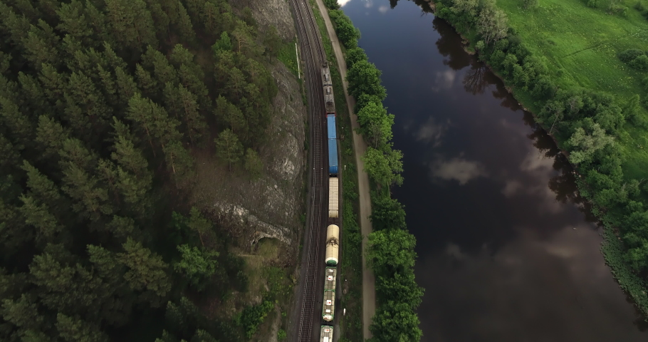 Freight long train carries with cargo carriages in a village in wild mountains landscape through a difficult part of Trans Siberian railways. Aerial drone wide view at summer day. Royalty-Free Stock Footage #1057662463