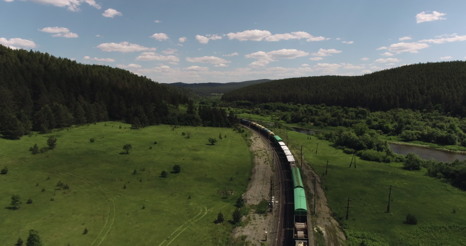 Freight long train carries with cargo carriages in a village in wild mountains landscape through a difficult part of Trans Siberian railways. Aerial drone wide view at summer day.