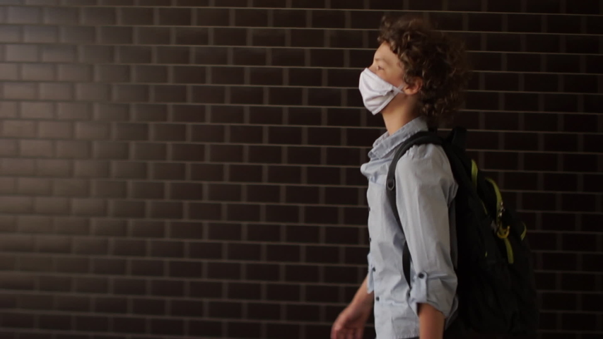 Back-to-school. A curly-haired schoolboy in a medical protective mask goes to school. A boy in a blue shirt carries a backpack behind his back, a child walks along an underground passage Royalty-Free Stock Footage #1057668874