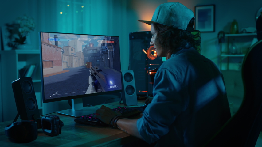 Professional eSports Gamer Plays 3D Shooter Mock-up Video Game with Lots of Action and Fun on His Powerful Personal Computer. Cyber Gaming Stylish Retro Neon Room
