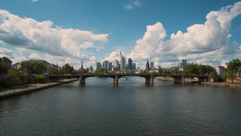 Frankfurt on a sunny summer day, river side with bridge in the foreground, cityscape and skyscrapers in the background, blue sky with big white clouds