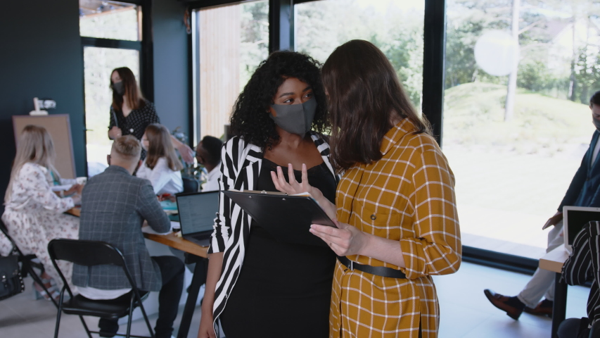COVID-19 safety at workplace. Happy young multiethnic female colleagues greet with elbows wearing masks at modern office Royalty-Free Stock Footage #1057684327