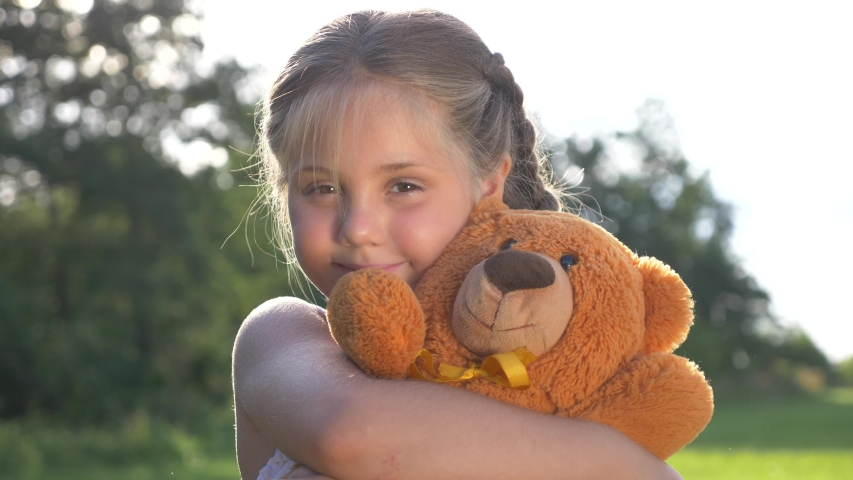 A little girl hugs her favorite toy. A child plays with a Teddy bear. A soft toy in the hands of a baby. A happy kid plays in the Park with a toy and dreams. Royalty-Free Stock Footage #1057685632