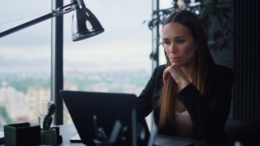 Focused businesswoman working on laptop computer in home office. Female manager typing on laptop keyboard indoors. Portrait of serious business woman looking at laptop screen in office Royalty-Free Stock Footage #1057689469