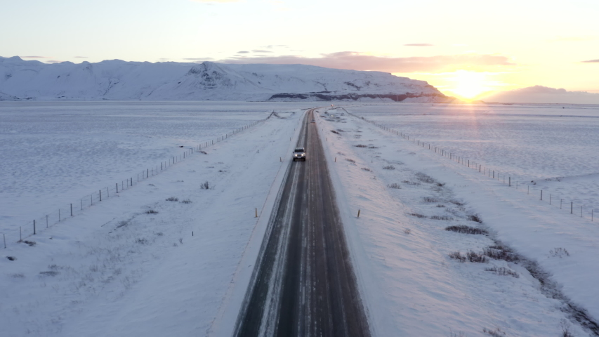 Wide Shot of Jeep Car driving on Iceland Road with Snow white Mountains and Sunset countryside, Winter, Aerial tracking dolly backwards | Shutterstock HD Video #1057692307