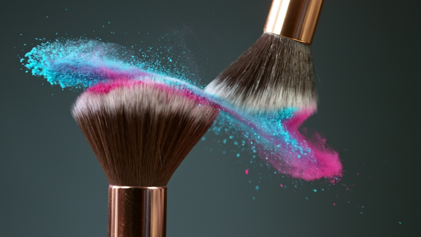 Makeup brushes touch each other on dark background and small particles of cosmetics, super slow motion, 1000 fps.