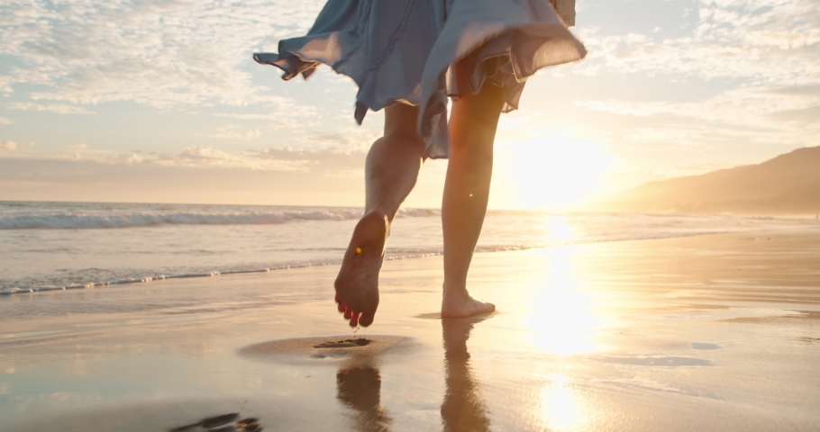 Slow motion woman feet walking barefoot by beach at golden sunset leaving footprints in sand. Female tourist on summer vacation in Malibu, California, USA. Woman in beautiful waving dress at sunset
