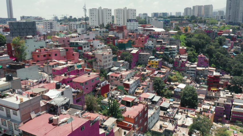Traveling Central America, exploring Mexico city. Pink low-income slum building in Mexico suburban. Vibrant favelas with Mexico city skyline on background. Colorful favelas in latin area. 4K aerial
