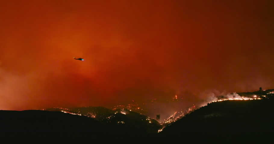4K epic shot of fire helicopter flying above wildfire. Thick plumes of hot orange smog and red flames rise from forest fire on mountain in Los Angeles suburban. Nature is burning due to climate change | Shutterstock HD Video #1057700155