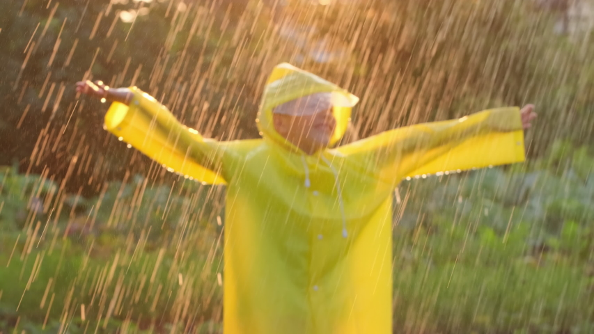 Little happy cute smiling boy child children raised hands in yellow raincoat  enjoying having fun rainfall. Kid playing with drops rain sunlight. Happy family summer autumn childhood dream concept 4 K