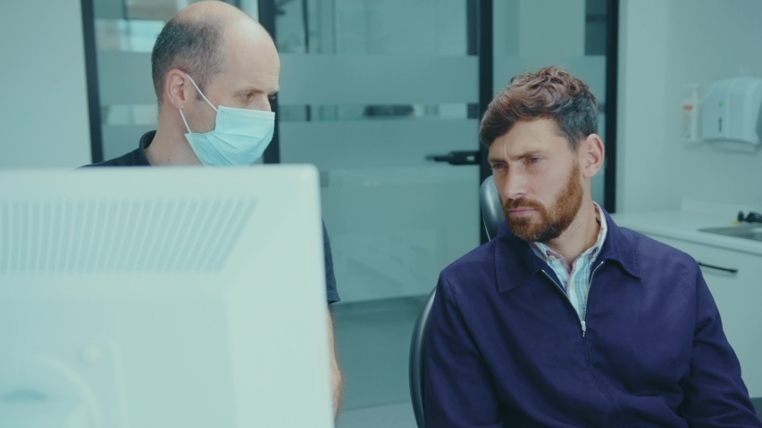 Close up man orthodontist dentist talks to a patient and shows problematic teeth on computer health care doctor clinic conversation diagnosis specialist slow motion Royalty-Free Stock Footage #1057703752