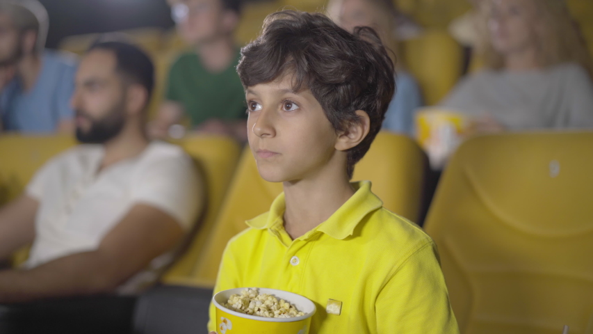 Cute Middle Eastern boy showing hush gesture in cinema. Portrait of happy little kid enjoying film in movie theatre. Handsome curly-haired child holding finger on lips and looking at camera. | Shutterstock HD Video #1057703893