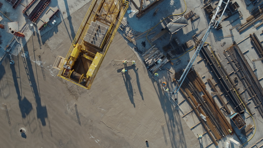 Aerial Flight Over a New Constructions Development Site with High Tower Cranes Building Real Estate. Heavy Machinery and Construction Workers are Employed. Top Down View at Contractors in Safety Hats. | Shutterstock HD Video #1057704832