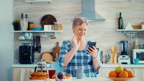 Senior woman waving during video conference using smartphone in kitchen while having breaksfat. Elderly person using internet online chat technology video webcam making a video call connection camera