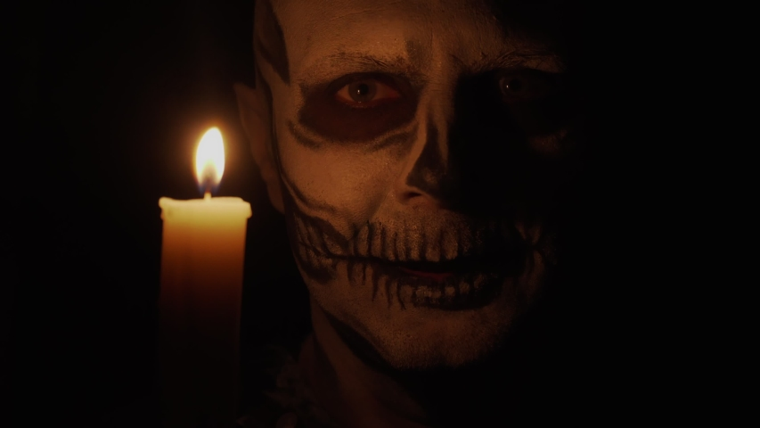 A man with skeletal makeup looks at the camera. The man is angry and casts a spell. Skeleton in the dim light of a candle. Halloween and horror concept. Royalty-Free Stock Footage #1057714606