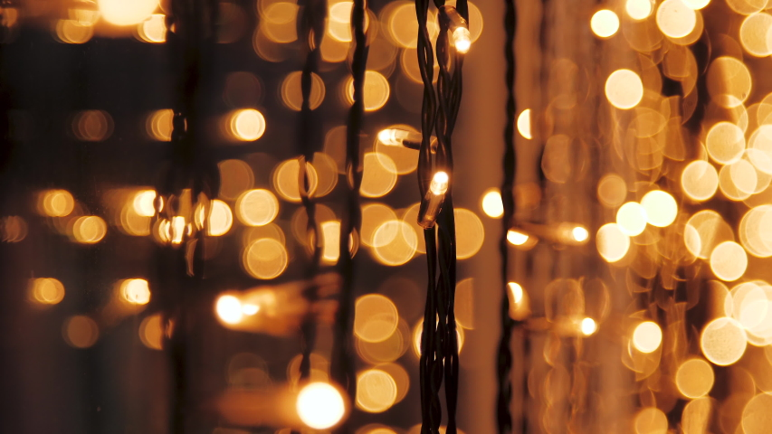 Decorative golden string lights hang and glow at evening, vintage garland of lamps, warm lighting, electric bulbs shining, decoration for holiday or christmas, blurry out of focus bokeh background Royalty-Free Stock Footage #1057720495