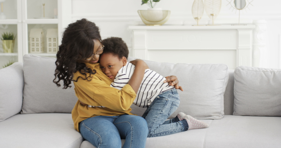 African American young pretty woman in glasses sitting on sofa at home and hugging her cute small daughter. Little girl embracing mother on couch in living room. Motherhood love. Happy safe childhood. | Shutterstock HD Video #1057729606