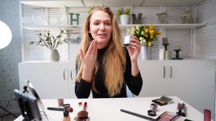 Beauty blogger woman filming daily makeup routine tutorial at camera on tripod. Influencer lady live streaming cosmetics product review in home studio. Vlogger female applies skin powder with brush.