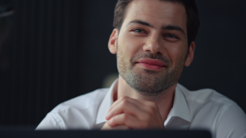 Happy businessman sitting at remote workplace with laptop. Portrait of smiling professional holding hand at face. Closeup dreamy business man dreaming in office. Top manager working in office Royalty-Free Stock Footage #1057746811