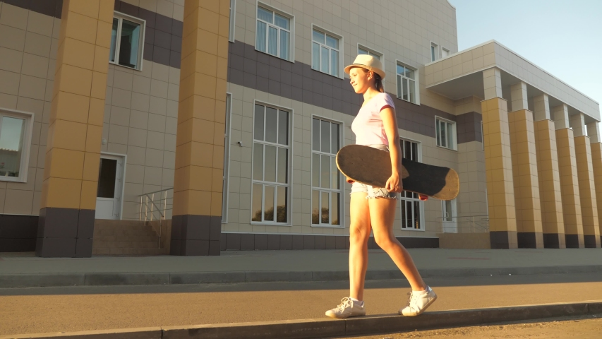 Sporty and healthy lifestyle of the modern teenager. Free teenage girl go with a skateboard in her hands on the street in city. happy skateboarder travels on road outdoors in the park.   Shutterstock HD Video #1057749229