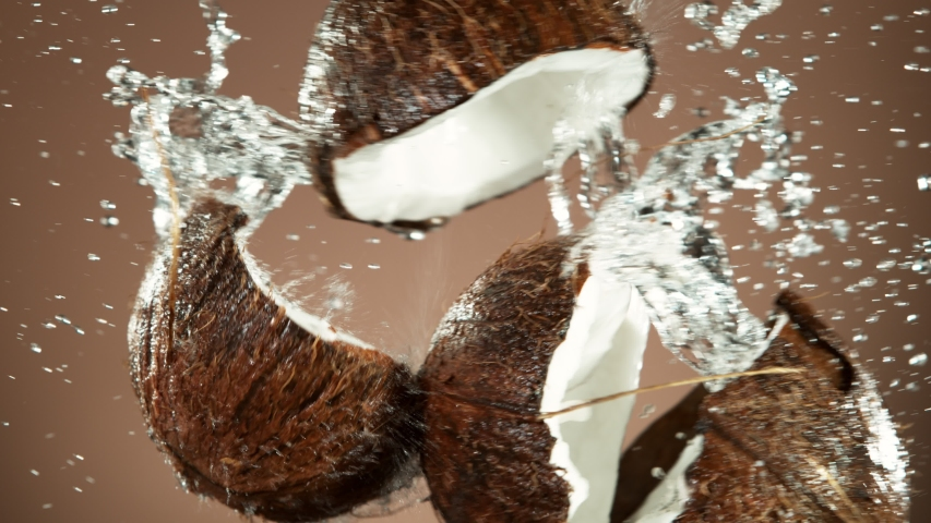 Super slow motion of coconut pieces flying in the air with water splashes. Filmed on high speed cinema camera, 1000 fps.