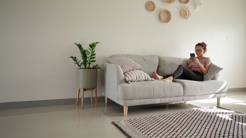 Relaxed young woman using smart phone surfing social media, checking news, playing mobile games or texting messages sitting on sofa. pretty woman spending time at home with smartphone. copy space shot Royalty-Free Stock Footage #1057758985