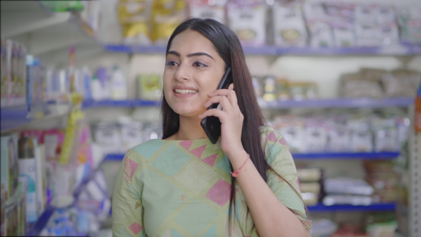 A young beautiful woman  is smiling and talking on a mobile while shopping for essential food in supermarket. A happy and attractive Indian girl is on a phone and buying groceries in a mall Royalty-Free Stock Footage #1057760815
