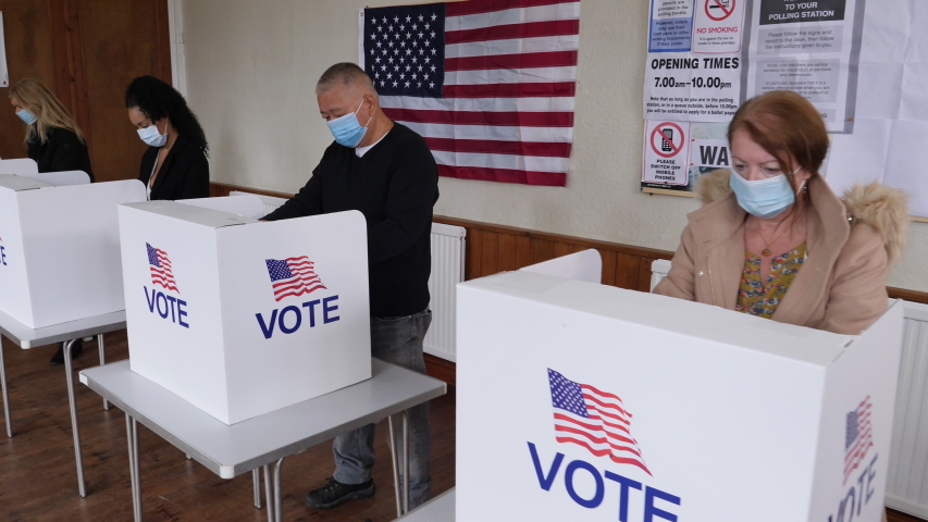 4K: Voters voting at Polling Place of the USA Election.  People Stood at booths wear Face Masks. Gimbal Walking shot. Stock Video Clip Footage | Shutterstock HD Video #1057761451