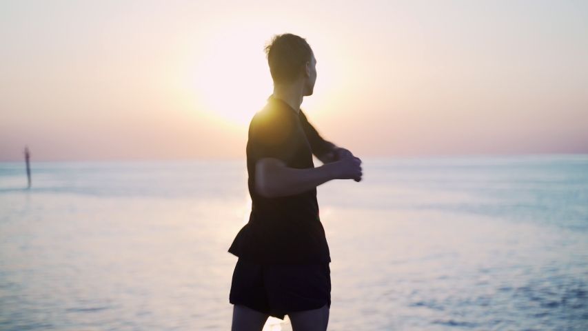 Morning workout. Warm up and stretching before training on the sea pier. Young man practicing against the backdrop of the sea and the rising sun. Sport activity. Athlete silhouette. Jumps ans squads. | Shutterstock HD Video #1057762102