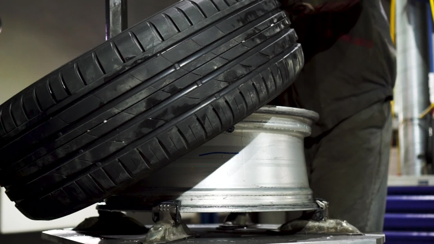 repairman mounting tire and inflate air with special device at service station. Footage. Replacement of car tire on steel disk. Royalty-Free Stock Footage #1057766644