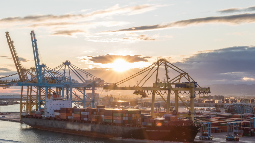 Aerial sunset view of the sea cargo port and container terminal of Barcelona with the Montjuic hill timelapse hyperlapse, Barcelona, Catalonia, Spain. Ships loading by cranes. View from cruise Royalty-Free Stock Footage #1057766971