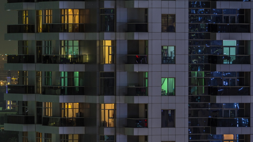 Rows of glowing windows with people in the interior of apartment building at night. Modern skyscraper from glass and concrete. Concept for business and modern life. Tilt down | Shutterstock HD Video #1057767028