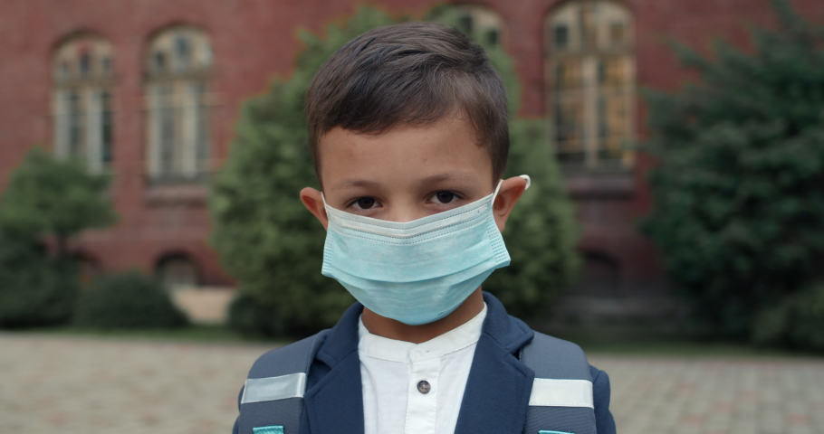 Portrait of kid boy wearing in medical protective mask looking to camera. Child with backpack wearing uniform posing while standing near school. Concept of children, education and virus Royalty-Free Stock Footage #1057768780