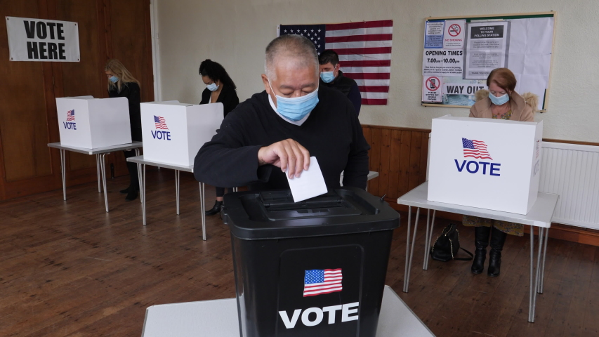 4K: Senior Male Chinese Voter voting at Polling Place for the USA Election. He wears a Face Mask while posting vote in the Ballot Box. Stock Video Clip Footage | Shutterstock HD Video #1057769458