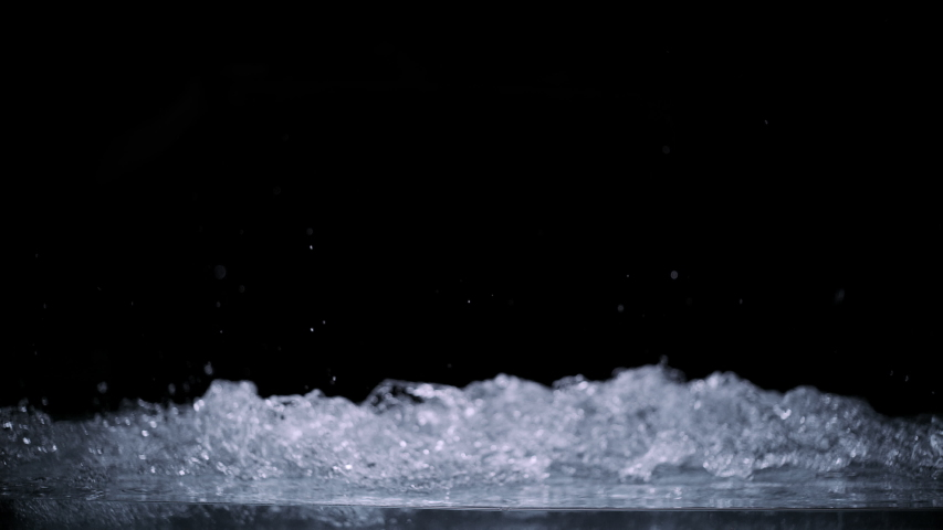 Abstract splashing water wave isolated on black background. Studio super slow motion shot with clear pure drinking water on cutout high key background splashing onto pov glass at high speed. | Shutterstock HD Video #1057771732
