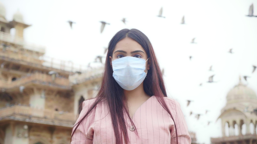 A young happy beautiful woman/ female is standing outdoors removes face protective/ surgical mask and smiles looking at camera or lens amid COVID 19/ Corona Virus epidemic or pandemic