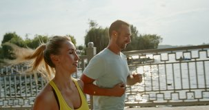 Positive athletes running on bridge near river. Tracking shot of happy couple in sportswear running on bridge near river during fitness workout on sunny day. 4K RAW video record