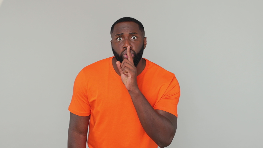 Young secret bearded african american man guy male in orange basic casual t-shirt looking around saying hush be quiet with finger on lips shhh gesture isolated on grey color gray background in studio | Shutterstock HD Video #1057782220