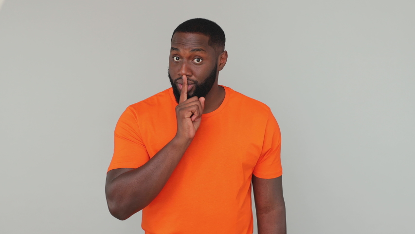 Young mysterious bearded african american secret guy 20s in orange basic casual t-shirt look camera saying hush be quiet with finger on lips shhh gesture isolated on grey color gray background studio | Shutterstock HD Video #1057782244
