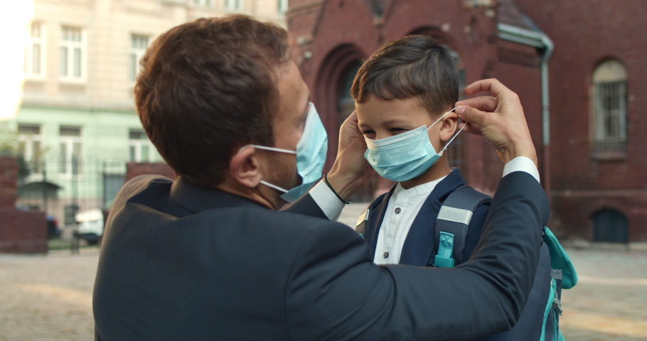 Close up of loving father wearing medical mask on his son face while sending him to school. Boy with backpack giving high five and running while man in suit standing and watching Royalty-Free Stock Footage #1057785592