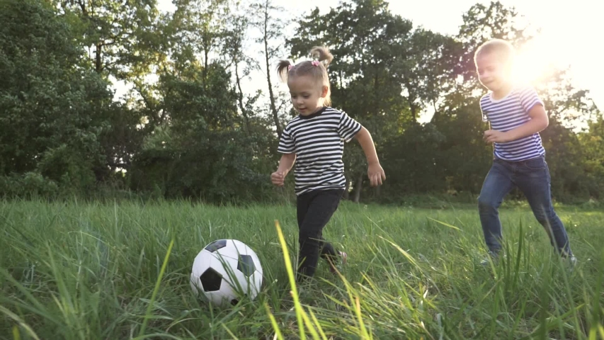 Happy family of children having fun in the park. Happy kids are run. Children run for a colorful ball in the park. Family at sunset in the park have fun playing with a ball. team dream of kids. Royalty-Free Stock Footage #1057788289