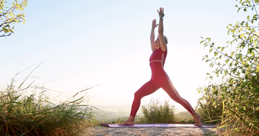 Beautiful adult woman doing perfect yoga poses Warrior Virabhadrasana III stretching and twisting exercises at sunrise