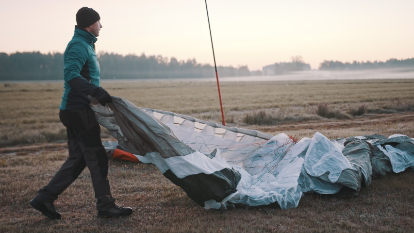 Paramotorgliding. Successfully landed, glider untying parachutist. High quality 4k footage