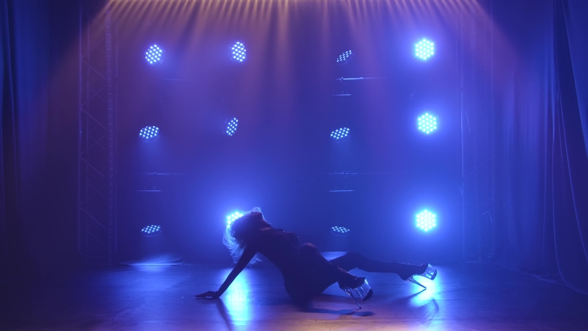 Sexy woman in stockings is dancing a Strip dance, strip of plastic. Silhouette of sensual blonde moving on a black background with blue spotlights. Slow motion.