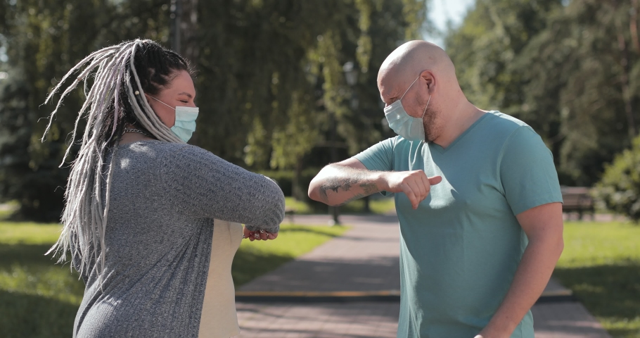Friends in protective medical face mask greet their elbows. Social distancing. Elbow bump is new greeting to avoid spread of coronavirus or covid-19 - Avoid or Stop handshakes due to pandemic.   Shutterstock HD Video #1057811587