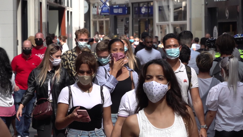 AMSTERDAM, NETHERLANDS – AUGUST 2020: Slow motion of people wearing face masks walking through busy shopping street in Amsterdam, coronavirus Covid-19 pandemic in Europe