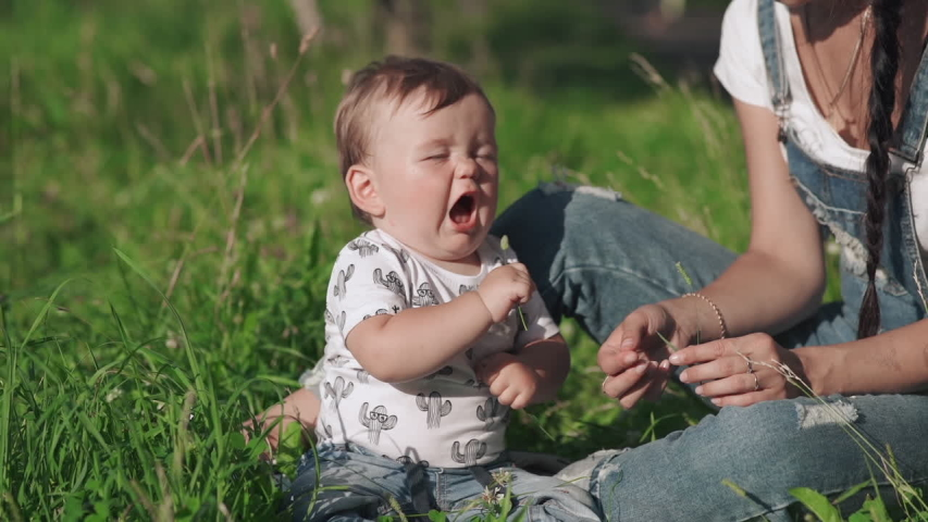 Beautiful young mother giving a small flower to her cute child. Pretty tender mommy and her little son sitting on the grass in the picturesque park. Concept of motherhood, love happiness and beauty.