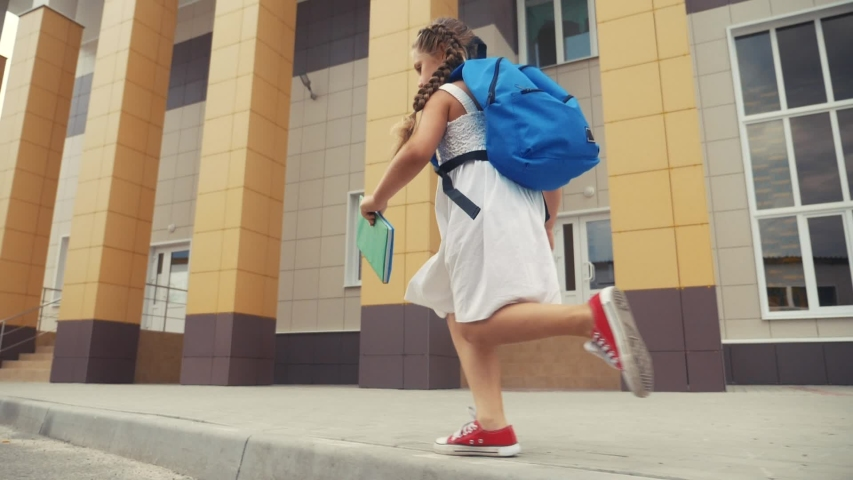 Little girl kid with a backpack and a textbook runs hurrying to school. fun education concept. little schoolgirl with a backpack runs to the school building. child running with textbook back view