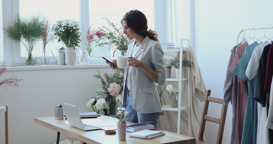Smiling young attractive female entrepreneur standing near working table, chatting in social networks by mobile application, resting with cup of hot coffee tea, communicating with clients online.