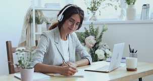 Smiling beautiful focused young female creative decorator florist in wireless earphones looking at laptop screen, watching educational lecture online seminar webinar, writing notes at workplace.